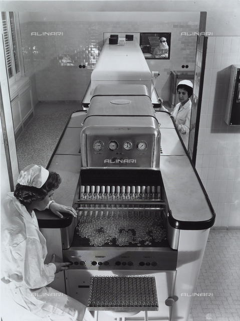 Top view of a machine in the Alfa factory with two workers.