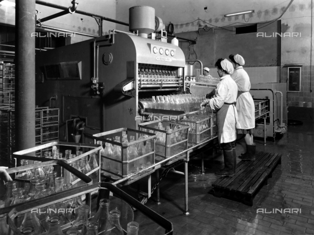 The inside of a Polenghi Lombardo factory. Two workers arranging bottles in a sterilization machine.