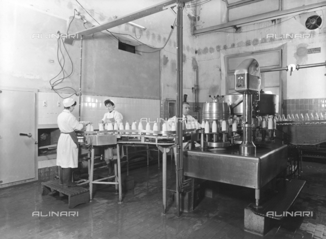 The inside of Polenghi Lombardo factory. Some workers operating a machine that applies labels to milk bottles