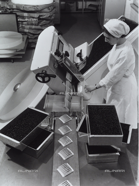 A worker operating a machine that packages medicine in vials in the Recordati chemical/pharmaceutical factory.
