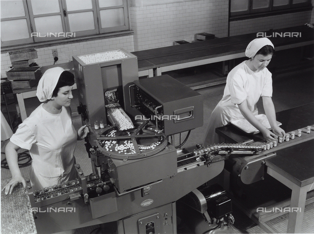 Recordati pharmaceutical factory. Machinery for the packaging of medicine tablets with workers closing the packages.