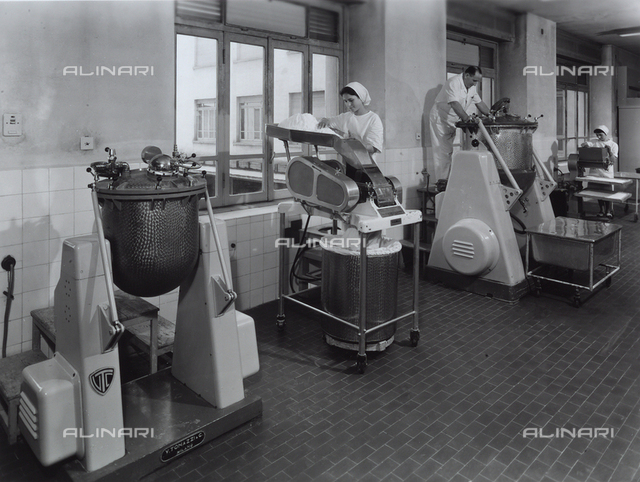 Three workers operating machinery at the Recordati pharmaceutical factory.