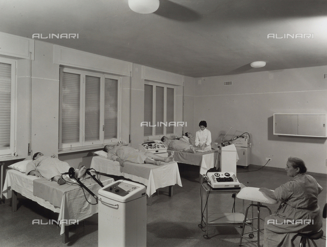 INAIL, Traumatological Institute of Budrio. Inside of a room with bedridden women and a doctor during therapy.