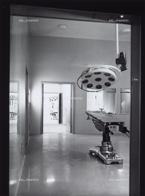 General Hospital. Photograph of an operating room with a bed and an overhead lamp.