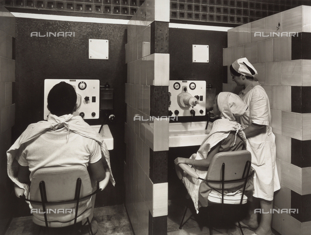Cervia Spa: inhalator room. Patients sitting in front of machines during therapy.