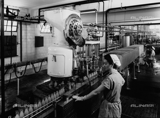 Inside of a SALFA factory. Two workers are monitoring the apparatus used for the capping of fruit juice bottles.