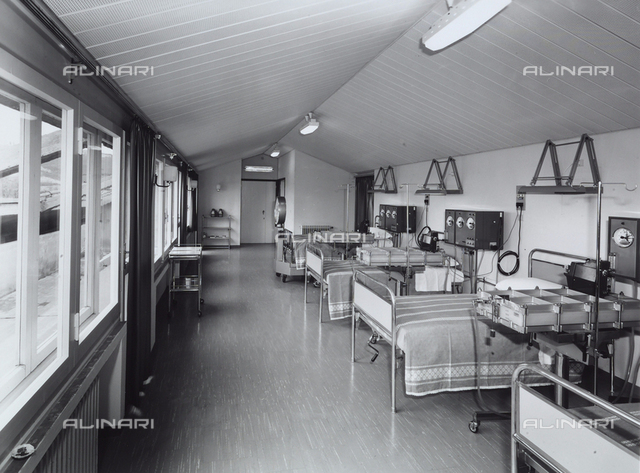 Inside of the Mapighi Hospital: large room with beds and machinery.