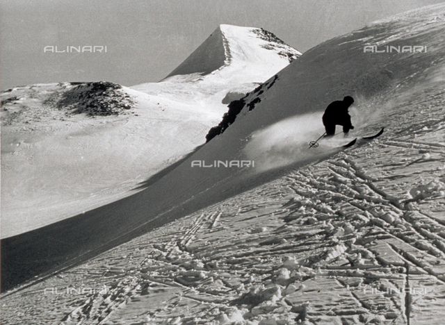 A snow-covered mountain landscape. In the distance a skier goes by. In the foreground: the ski tracks that have passed over the untouched surface of the snow