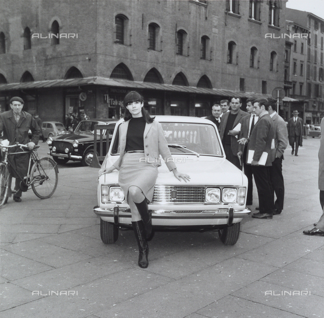 Woman advertises the new Fiat 125 on the Piazza Grande, Bologna