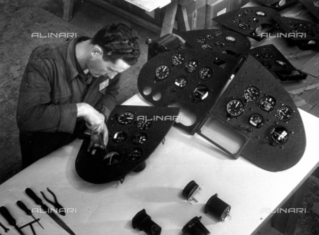 A technician busy fitting various instruments on a control panel in the Caproni indutry