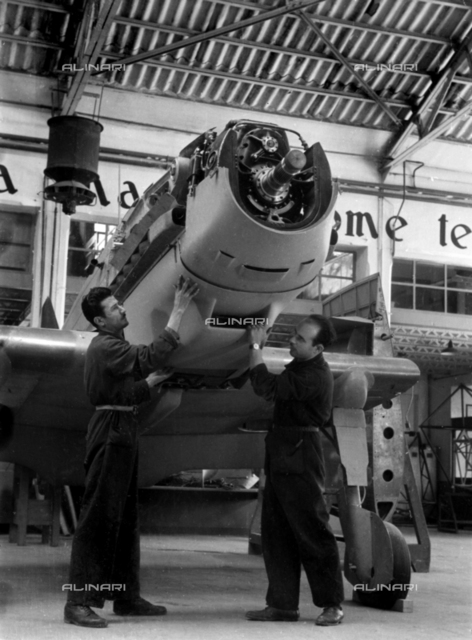 An airplane under construction inside a Caproni hangar. Two technicians are inspecting the aircraft