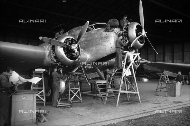 A group of technicians building an airplane inside a hangar of Caproni factory