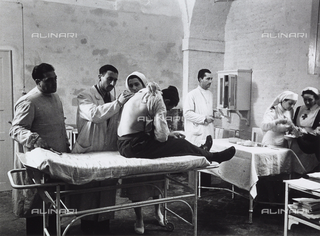 Doctors visiting patients with the assitance of the Red Cross in a hospital during World War II.