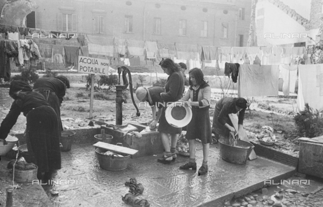 Hanging clothes and women at the fountain during the laundry