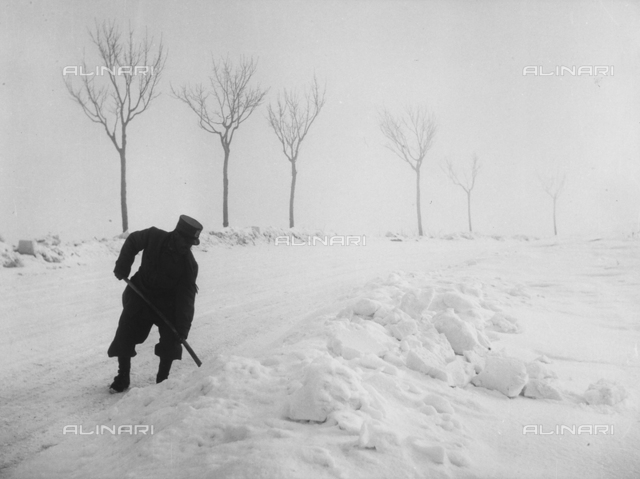 A man, on a snow-covered street, shoveling snow to the side of the road.