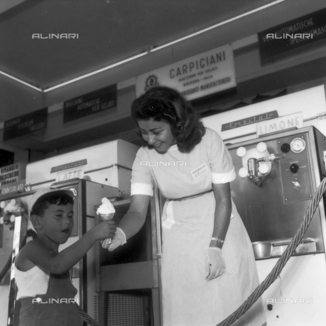 Child receives an ice cream from a woman who works at an ice cream shop