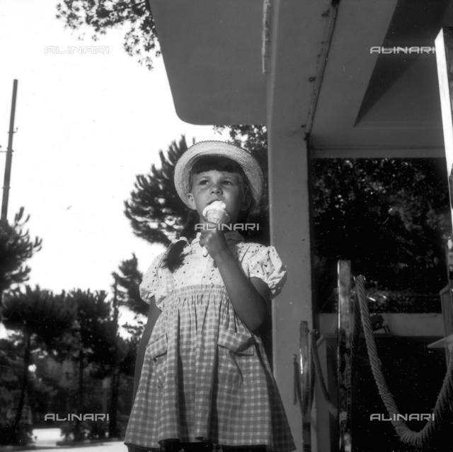 Girl walking on the street eating an ice cream