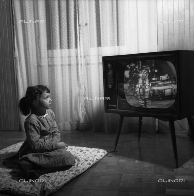 Girl in front of a television looks at the Japanese toys advertising