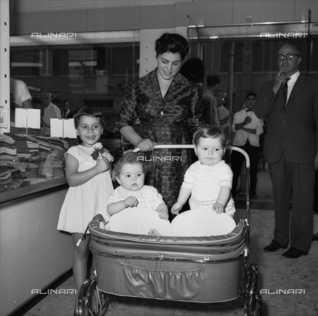Mother with children in wheelchairs in the Store UPIM, Bologna