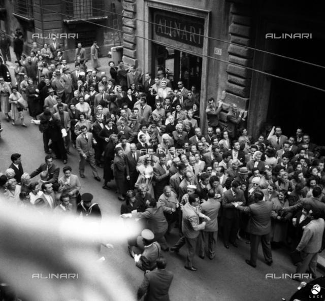 Grace Kelly and Prince Ranieri III in Rome: Crowd in Via del Corso awaiting the arrival of Monaco princes. In the background, the Alinari store