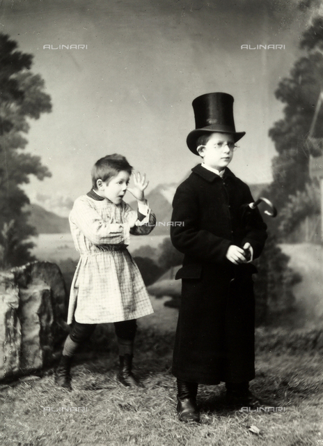 Portrait of the Wulz brothers, Antoniio and Guglielmo. One of the brothers is wearing a overcoat and top hat; while behind him, his younger brother is making funny faces