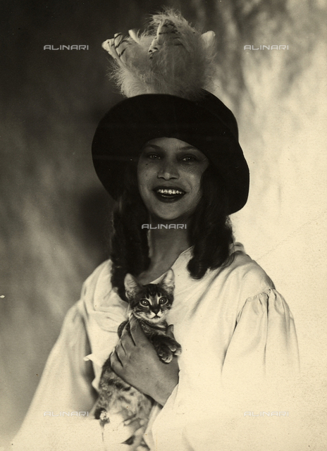 Portrait of the photographer, Marion Wulz, holding a kitten and wearing a dark, feathered hat
