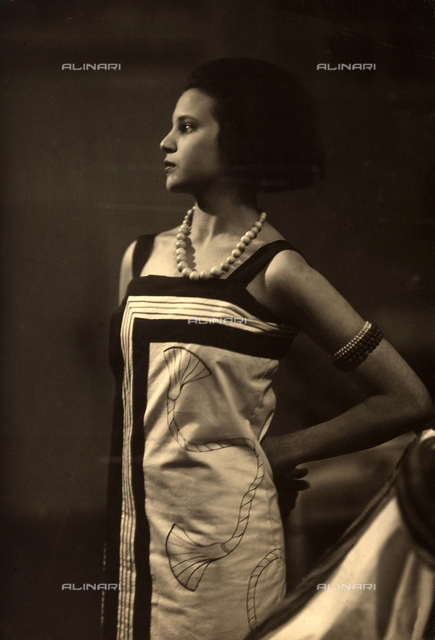 Profile portrait of the photographer, Marion Wulz, wearing a long, sleeveless dress, completmented with a large neckalace and bracelets
