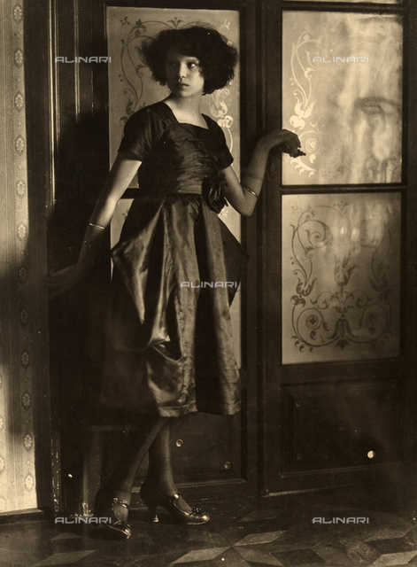Full-length portrait of the photographer, Marion Wulz, wearing an elegant, dark dress. The glass door behind her, allows subtle light to filter in