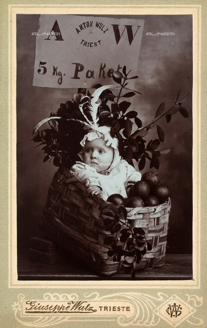 Wanda Wulz as a child in a basket with fruits and branches