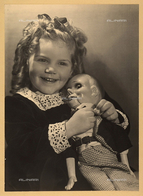 Portrait of Selma Stultus as a child, smiling and huging her doll