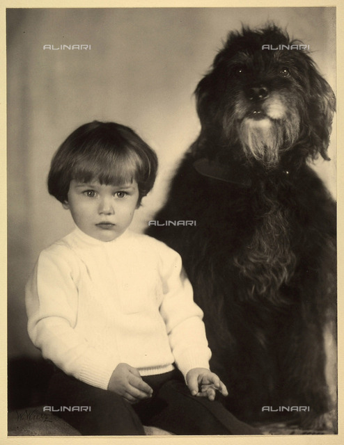 Portrait of a child seated next to his dog