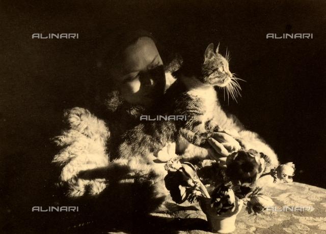 Ritratto di Wanda Wulz, con la gatta Mucincina, appoggiata ad un tavolo. In primo piano un piccolo vaso con fiori.