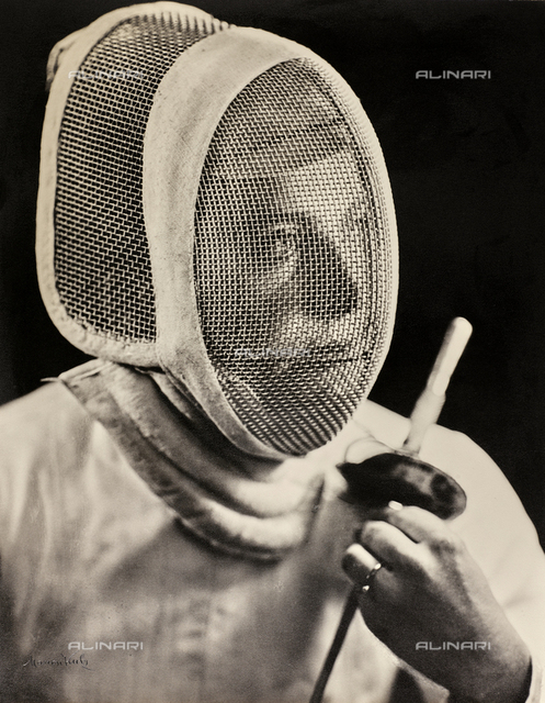 Portrait of the fencer, Irene Camber, gold medalist at the 1952 Olympic games in Helsinki, with her face covered by the fencing mask
