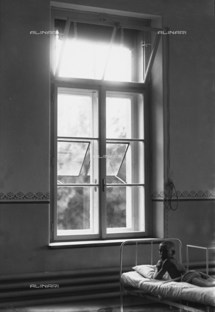 Child laying on a bed, in a room of the Duchessa Elena d'Aosta hospice, Valdoltra, Trieste