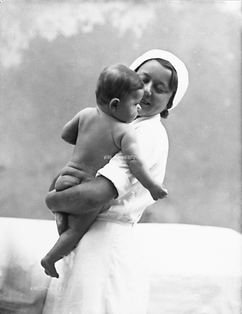 "Nurse with newborn posing for the book ""La ginnastica del lattante"" (Infant Exercises) by Eugenio Paulin"