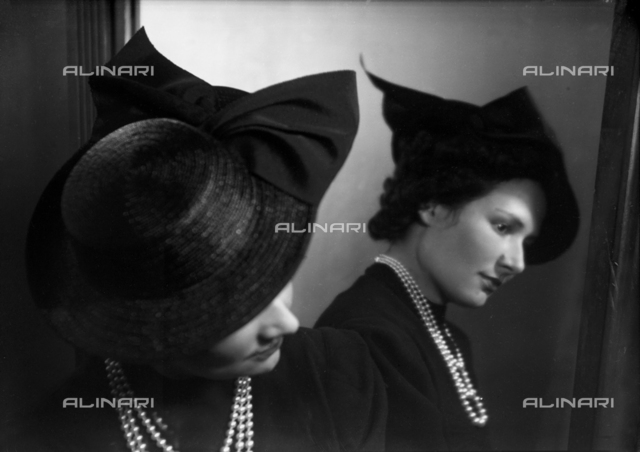 Portrait of a woman in front of a mirror with hat and necklace