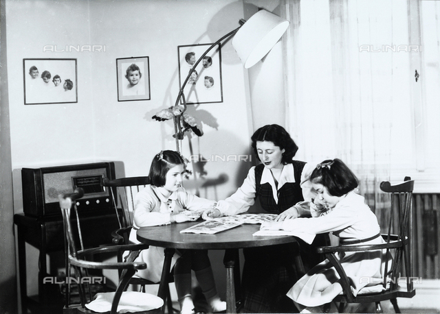 Mrs. Trakakis with her daughters, sitting at a table in the lounge