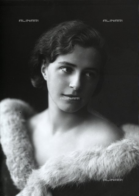Portrait of a young woman with a low-necked dress and a fur collar