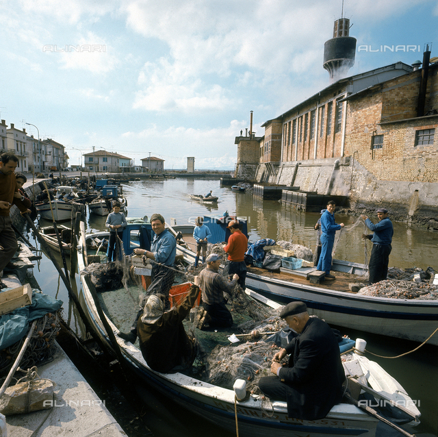 Fishermen at work on boats tied up along the canal of Murano, in the Venetian lagoon