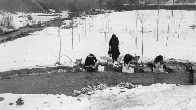 Snowy landscape with women doing laundry on the banks of a river